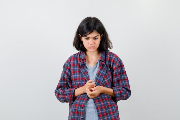 Tienermeisje kijkt neer in vrijetijdskleding en kijkt neerslachtig, vooraanzicht.