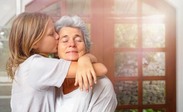 Tienermeisje knuffels en kusjes met liefde senior vrouw binnen