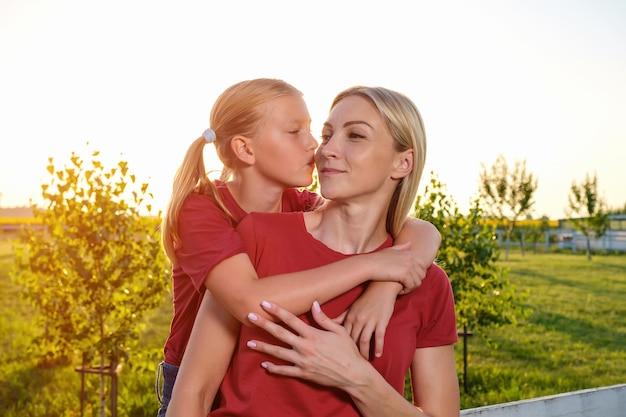 Tienermeisje knuffelt en kust gelukkig haar moeder in de natuur bij zonsondergang