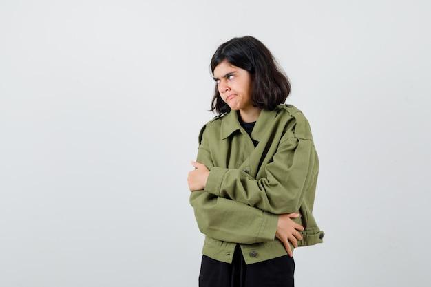 Tienermeisje knuffelt zichzelf, kijkt opzij, gebogen lippen, fronsend gezicht in legergroen jasje en kijkt hatelijk, vooraanzicht.