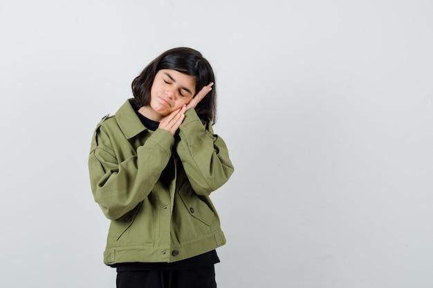 Tienermeisje leunt op de hand als kussen in t-shirt, groene jas en ziet er slaperig uit, vooraanzicht.