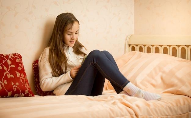 Tienermeisje liggend op bed met haar privé dagboek
