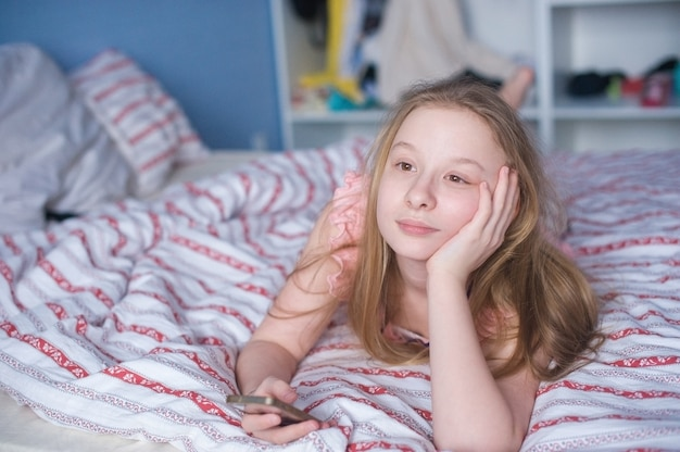 Tienermeisje liggend op bed met telefoon