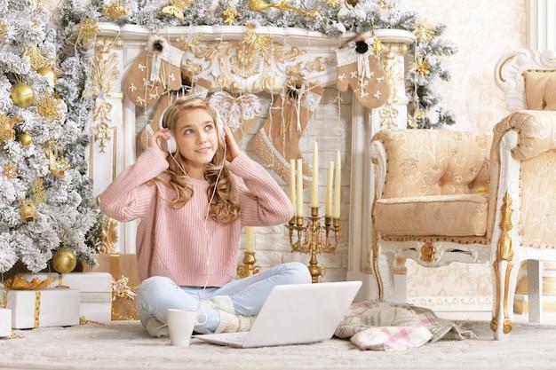 Tienermeisje met behulp van laptop zittend op de vloer in de kamer versierd met kerstvakantie