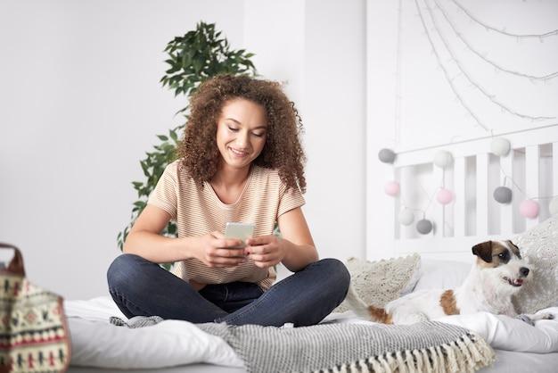 Tienermeisje met behulp van mobiele telefoon in haar slaapkamer