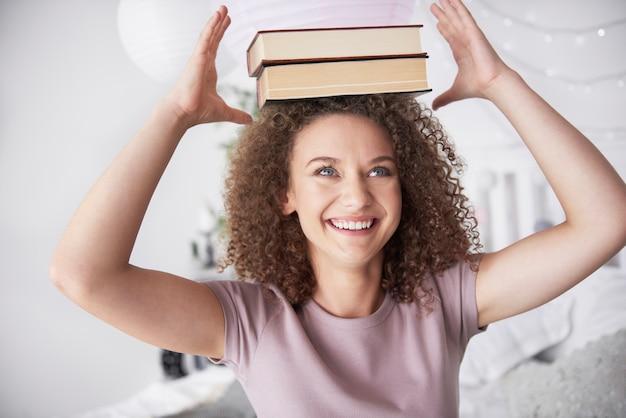 Tienermeisje met boeken op haar hoofd