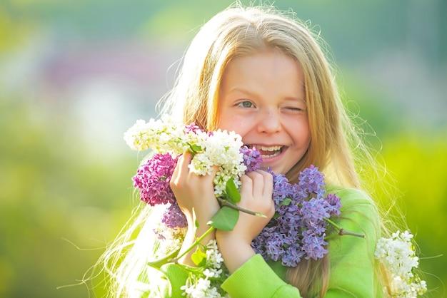 Tienermeisje met boeket van paars en wit lila knipogen. grappig lachend tienermeisje met lentebloemen.