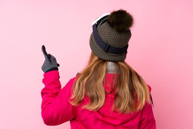 Tienermeisje met de winterhoed over geïsoleerde roze muur