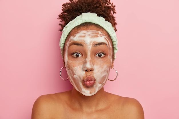 Tienermeisje met donkere huid heeft een problematische huid, past schuim toe op natter gezicht, houdt de lippen gevouwen
