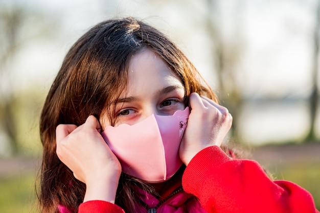 Tienermeisje met een beschermend masker gemaakt van roze stof op straat.