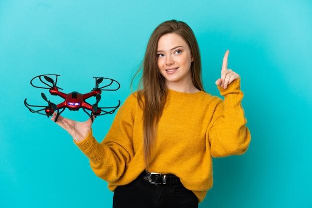 Tienermeisje met een drone over een geïsoleerde blauwe achtergrond die een geweldig idee benadrukt