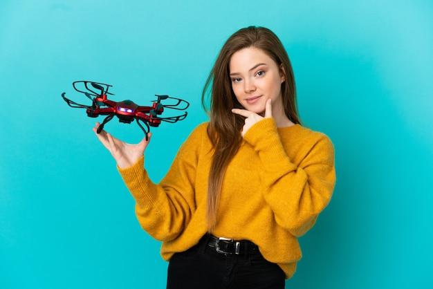 Tienermeisje met een drone over geïsoleerde blauwe achtergrond denken