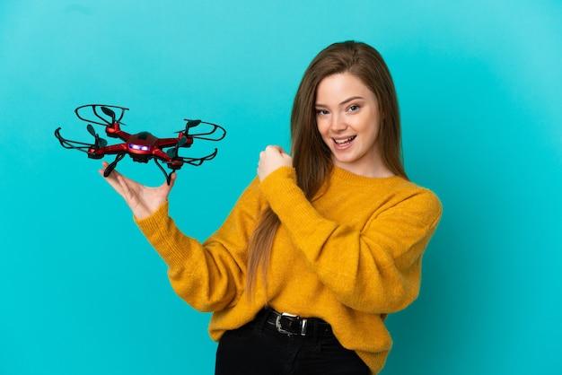 Tienermeisje met een drone over geïsoleerde blauwe achtergrond die een overwinning viert
