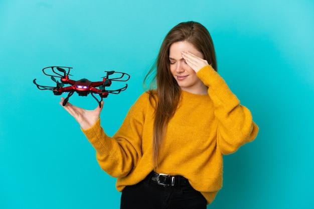 Tienermeisje met een drone over geïsoleerde blauwe achtergrond lachen
