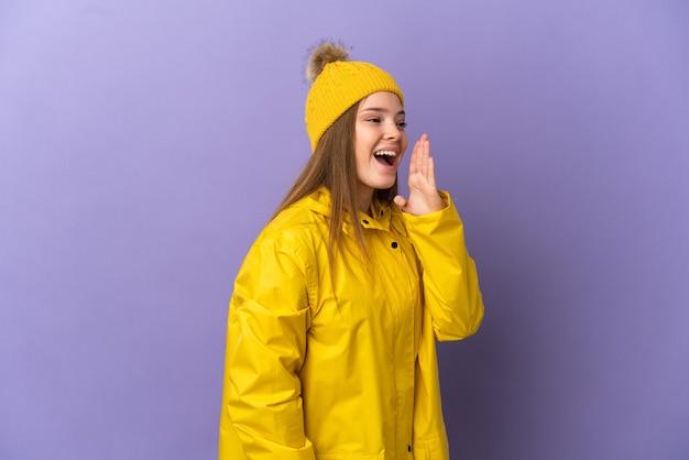 Tienermeisje met een regenbestendige jas over een geïsoleerde paarse achtergrond en schreeuwt met wijd open mond naar de zijkant