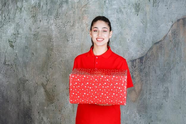 Tienermeisje met een rode geschenkdoos met witte stippen erop.