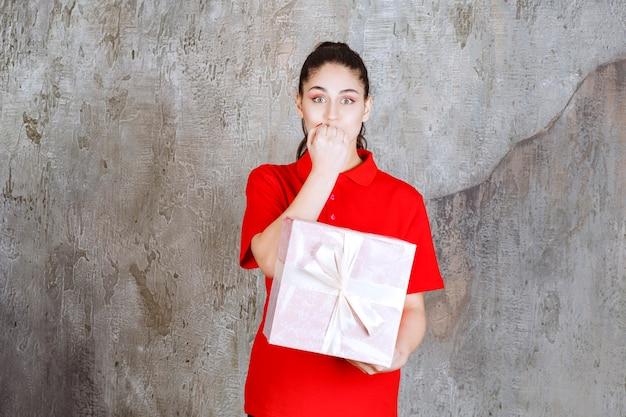 Tienermeisje met een roze geschenkdoos omwikkeld met wit lint en ziet er gestrest en nerveus uit.