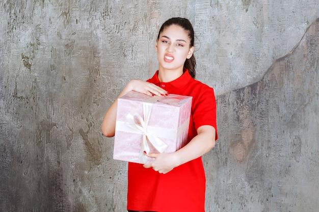 Tienermeisje met een roze geschenkdoos omwikkeld met wit lint en ziet er ontevreden uit