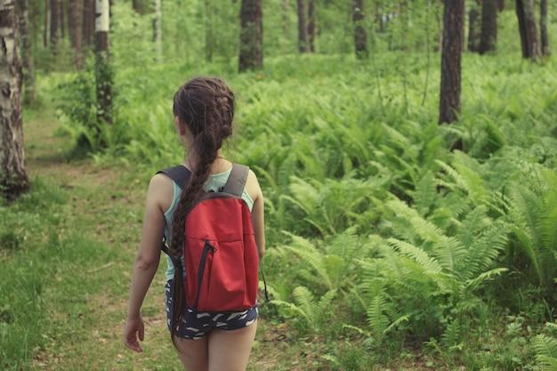 Tienermeisje met een staartje, in blauwe korte broek, met een rode rugzak reist langs een pad in een groen zomerbos.