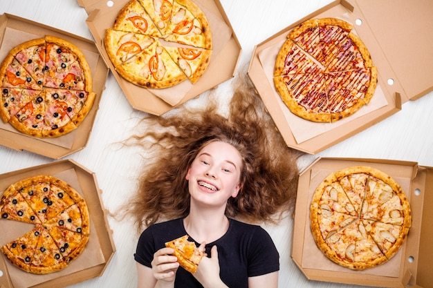 Tienermeisje met een stuk pizza in haar handen en pizzadozen om haar leugens