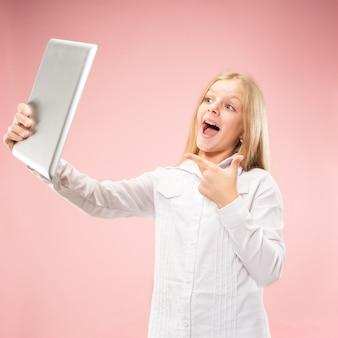 Tienermeisje met een tablet. aantrekkelijk vrouwelijk half-lengte voorportret, trendy roze studio achtergrondgeluid.