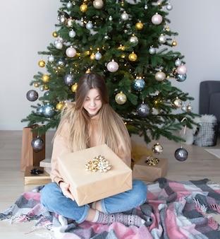 Tienermeisje met geschenken in de buurt van de kerstboom. woonkamer interieur met kerstboom en versieringen. nieuwjaar. cadeaus geven.