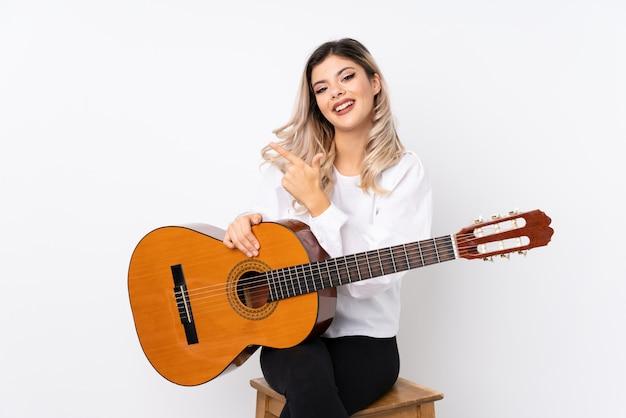 Tienermeisje met gitaar over geïsoleerd wit die aan de kant richten om een product te presenteren