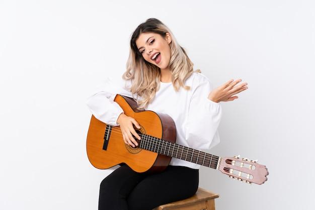 Tienermeisje met gitaar over geïsoleerd wit met geschokte gelaatsuitdrukking