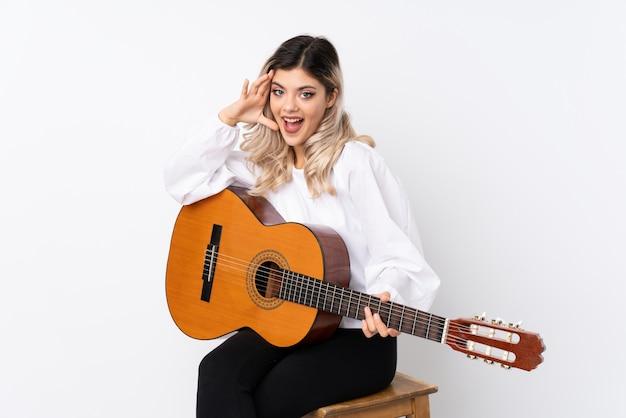 Tienermeisje met gitaar over geïsoleerd wit met verrassing en geschokte gelaatsuitdrukking