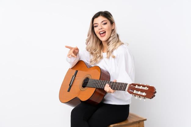Tienermeisje met gitaar over geïsoleerd wit verrast en wijzende vinger aan de kant