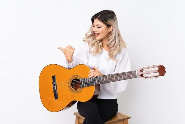 Tienermeisje met gitaar over geïsoleerde witte achtergrond die aan de kant richten om een product te presenteren