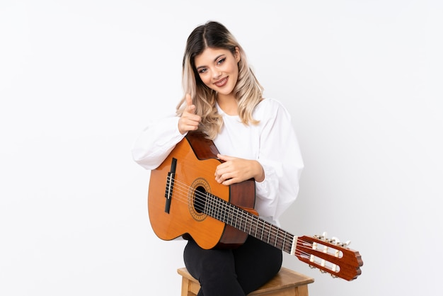 Tienermeisje met gitaar over geïsoleerde witte puntenvinger bij u met een zekere uitdrukking