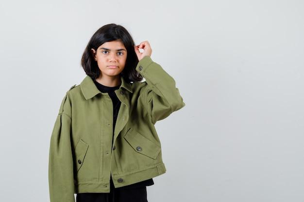 Tienermeisje met haarlok in t-shirt, groen jasje en voorzichtig kijkend. vooraanzicht.