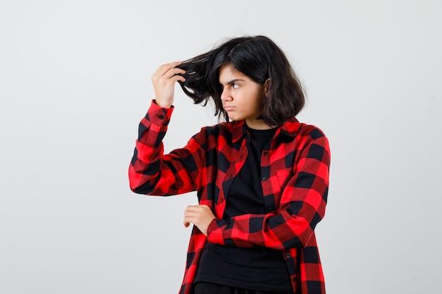 Tienermeisje met haarlokken in t-shirt, geruit hemd en gefocust, vooraanzicht.