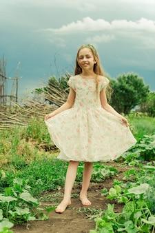 Tienermeisje met lang haar in een jurk op een achtergrond van de natuur