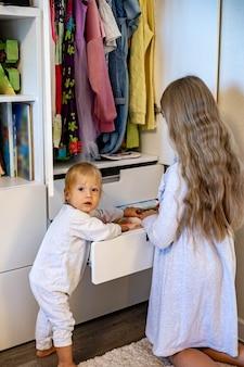 Tienermeisje met lang haar opgerolde kleding gebruikt de marie kondos-methode om kleding in de kast te plaatsen