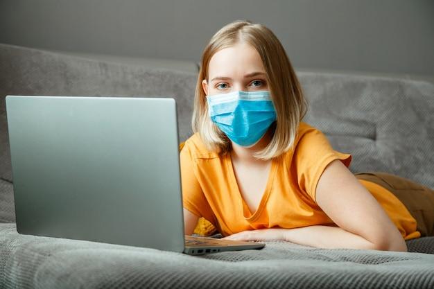 Tienermeisje met masker doet online leeronderwijs via laptop covid 19 lockdown-tijd. werken op afstand in de pandemie van het coronavirus. vrouw met medisch beschermend masker werkt met laptop op kantoor aan huis ligt op de bank.