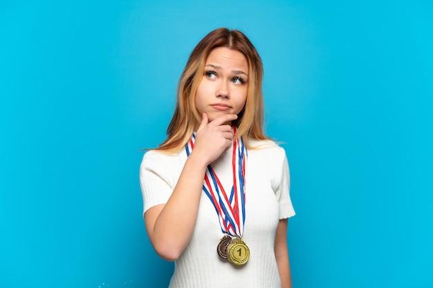 Tienermeisje met medailles geïsoleerd met twijfels