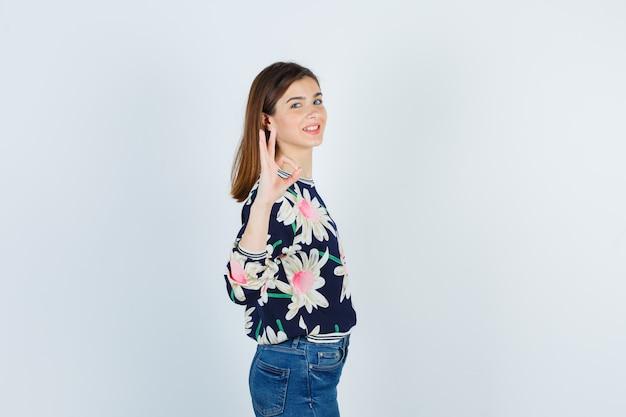 Tienermeisje met ok gebaar in blouse, spijkerbroek en zelfverzekerd kijken. vooraanzicht.