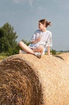 Tienermeisje met plezier in een tarweveld op een zomerdag. meisje op de hooibaal tijdens de oogsttijd.