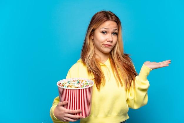 Tienermeisje met popcorns geïsoleerde blauwe achtergrond die twijfels heeft terwijl ze handen opsteekt