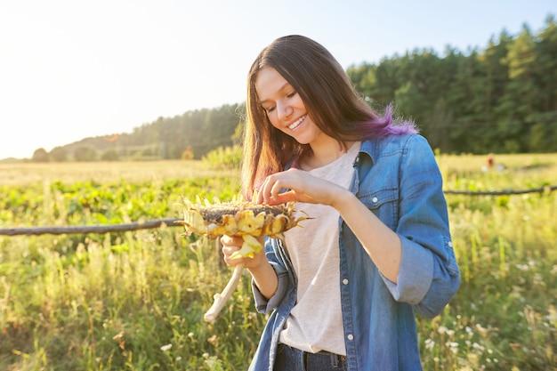 Tienermeisje met rijpe zonnebloeminstallatie. herfst natuurlijke landschapsachtergrond, zonsondergang, gouden uur, kopieer ruimte