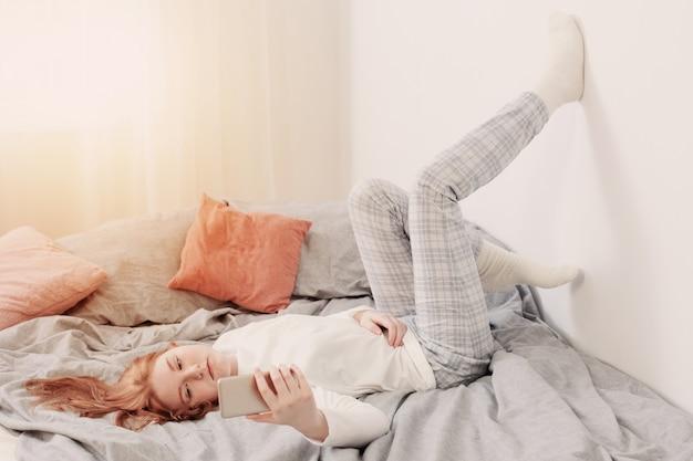 Tienermeisje met smartphone op bed