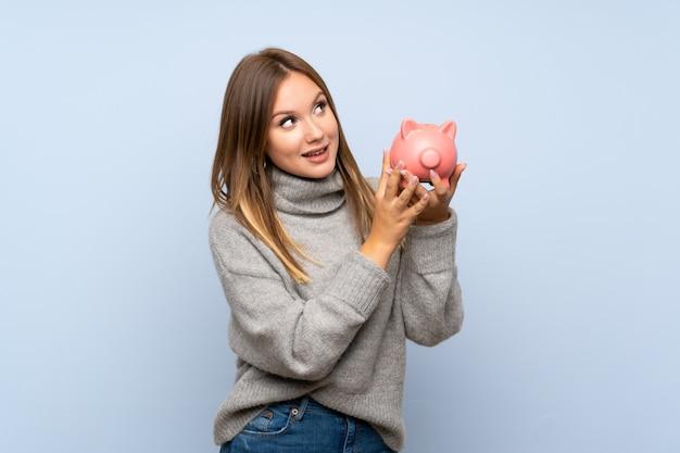 Tienermeisje met sweater over geïsoleerde blauwe achtergrond die een grote spaarpot houden