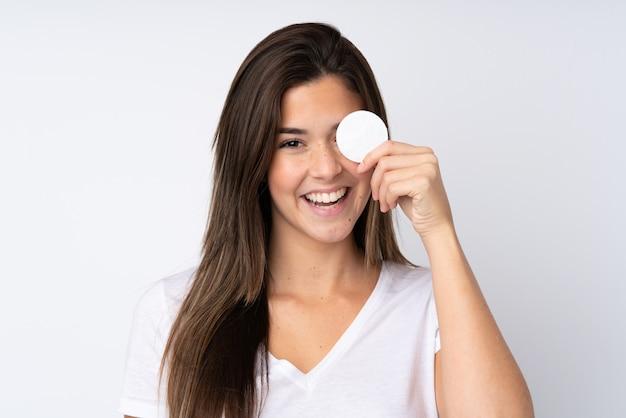 Tienermeisje met wattenschijfje voor het verwijderen van make-up uit haar gezicht en het glimlachen