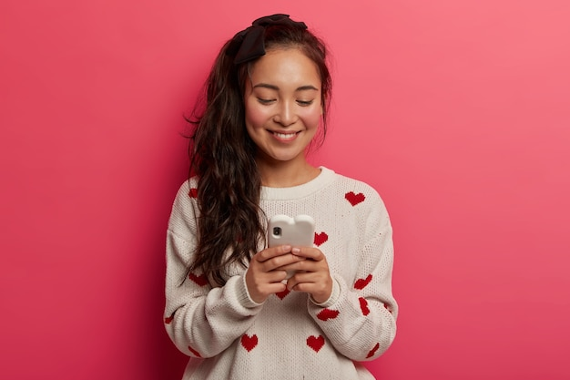 Tienermeisje met zachte glimlach, typt berichten op moderne mobiele telefoon, chats online, leest post in sociale netwerken, heeft technologieverslaving