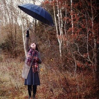 Tienermeisje met zwarte paraplu in de herfstbos