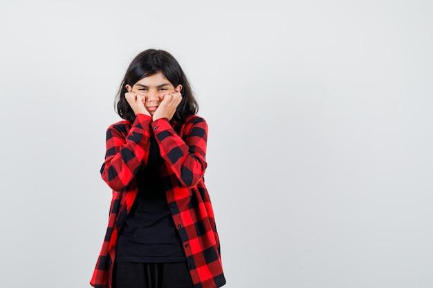 Tienermeisje mokkend met wangen op handen in t-shirt, geruit hemd en verveeld op zoek. vooraanzicht.