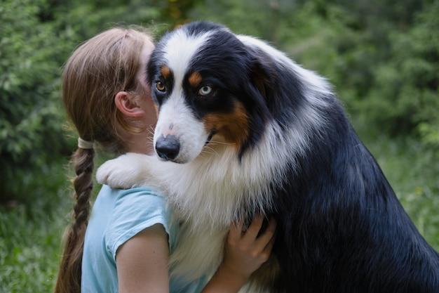 Tienermeisje omhelst australische herder drie kleuren hond in de zomer. beste vrienden. huisdieren zorgconcept. liefde en vriendschap tussen mens en dier.