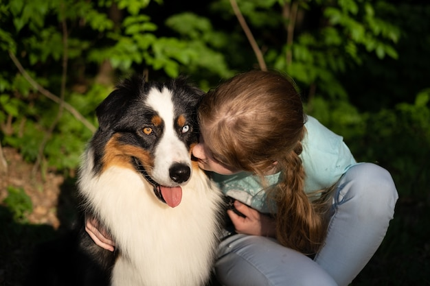 Tienermeisje omhelzing kus australische herdershond. huisdieren zorgconcept. liefde en vriendschap